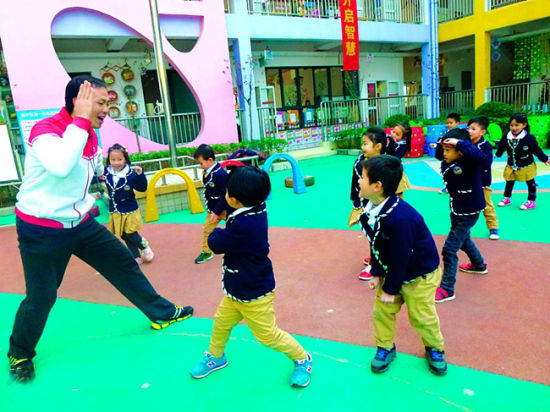 """唐咸武老师带领孩子们做""""我们都是木头人""""的游戏热身。记者 蒋晓梅 摄"""