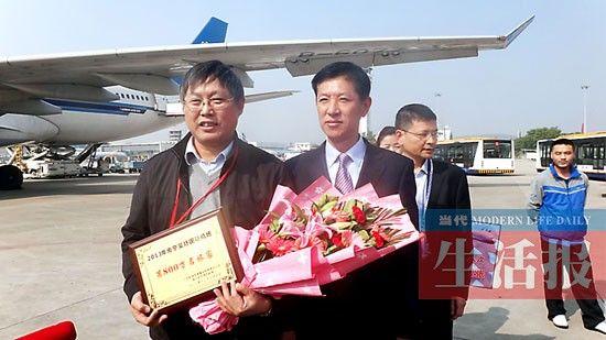南宁机场第800万名旅客(左)与南宁机场总经理刘丹合影。