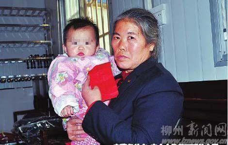 图为在警务站内,韦女士抱着可爱的女婴。