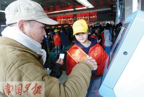 志愿者(右)在自动售票厅前为旅客服务。