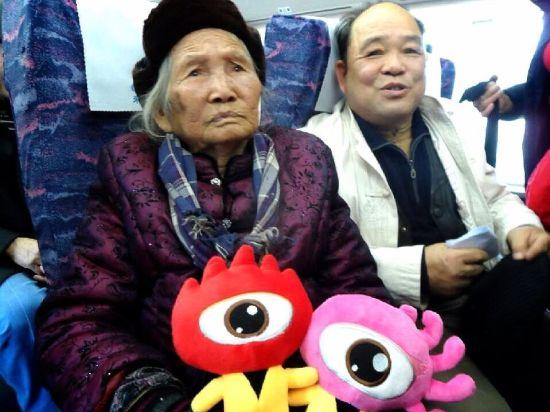 百岁老太坐在动车上,跟前摆着两只新浪公仔。