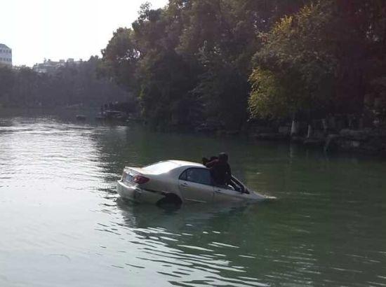 小车落水后,两名女子从车窗里爬出。丘清泉 摄