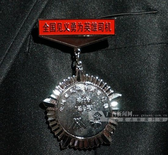 """英雄司机田爱民说,""""全国见义勇为司机""""的奖章对自己是纪念,同样也是鞭策。广西新闻网记者 刘斐 摄"""