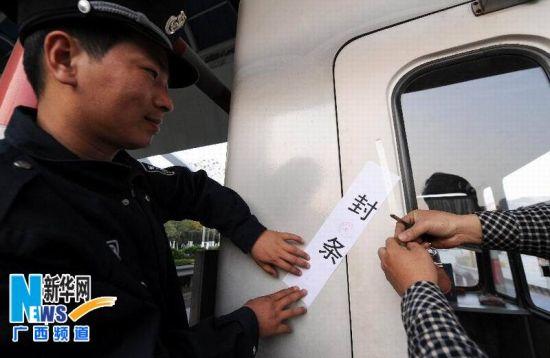 2013年12月31日,工作人员在柳州市柳石收费站给收费窗口贴上封条。 新华社记者 李斌 摄