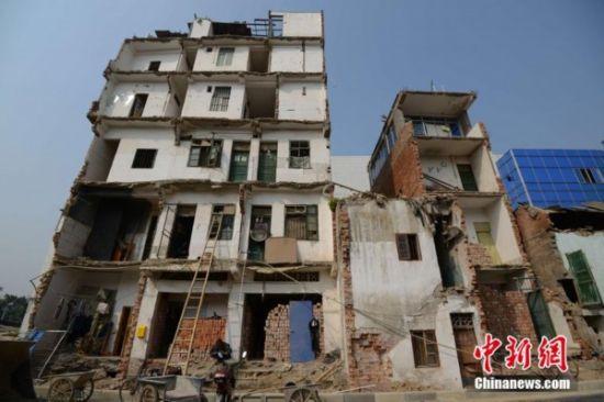"""长堽路扩建路段两边出现了两排之前因为拆迁遗留下来的""""危楼景观""""楼房 图片来源:中新网"""