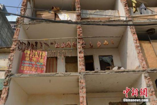路边很多楼房都是只拆掉一半,另一半没拆掉的就像危楼一样依然矗立在那里。图片来源:中新网