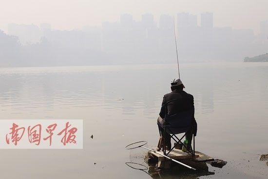 1月1日,葫芦鼎大桥下,一名正在钓鱼的市民所在不远处,高楼像飘在云中雾里。南国早报记者 邹财麟 摄