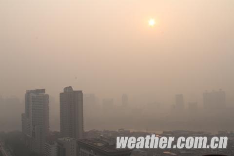 """南宁市区今早8~9时之间的太阳掩埋在严重霾里,如""""日晕""""(图谢晓琳)"""