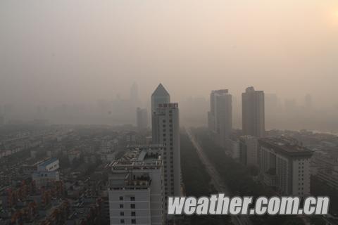 """南宁市区的雾霾遮挡了城市的""""楼宇"""",也影响了人们出行的心情。双休日本该热闹出行,可是街道却冷冷清清。(图谢晓琳)"""