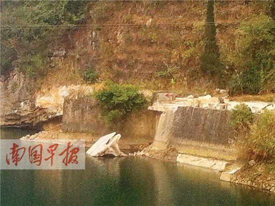 桥垮塌后,河边露出一小块桥面。记者 蓝锋 摄