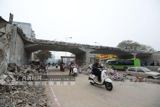 图为人们从拆除的桥下经过。