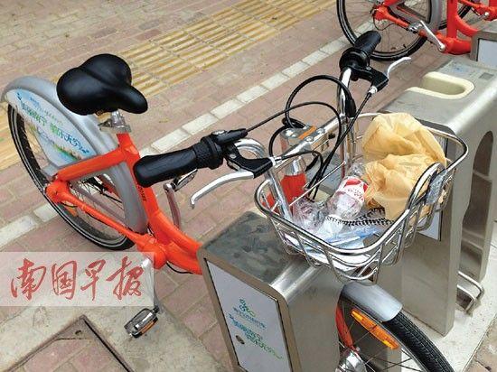 有市民把垃圾随手扔在公共自行车的篮子里。图片来源:南国早报