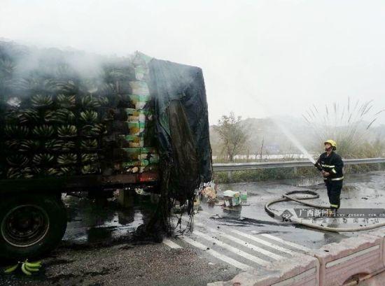 图为消防部门正在紧急灭火。裸露在外的香蕉均已烧黑。