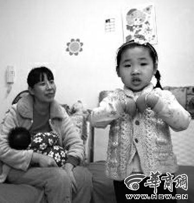 5岁的钱柳伊表演儿歌,妈妈抱着妹妹看她表演节目。在两个月前,钱柳伊升级为姐姐了,因为她有了妹妹 本报记者 王警 摄