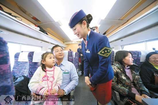 """南宁铁路局的动车乘务员正热情地为旅客提供"""" 快旅时代""""的服务。记者黄克 通讯员陈孚平 摄"""
