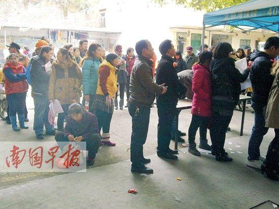 南宁市中山社区,一名等待上牌的市民等得太久,只好掰菜打发时间。南国早报记者 邓晓衡 摄