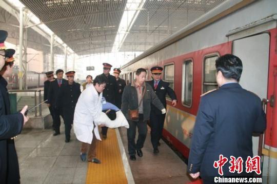 一路奔波后,吴州终于被抬进列车。董伟 摄