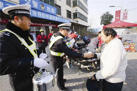 在休息点,执勤交警为摩托车司机送上热乎乎的姜糖水。南国早报记者 苏华 摄