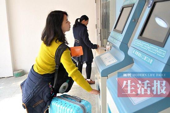 旅客在自助售(取)票机前取票。图片来源:当代生活报