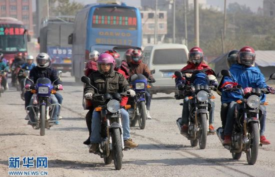 1月21日,在粤桂交界的广西梧州市藤县路段,众多返乡摩托车在行进中。
