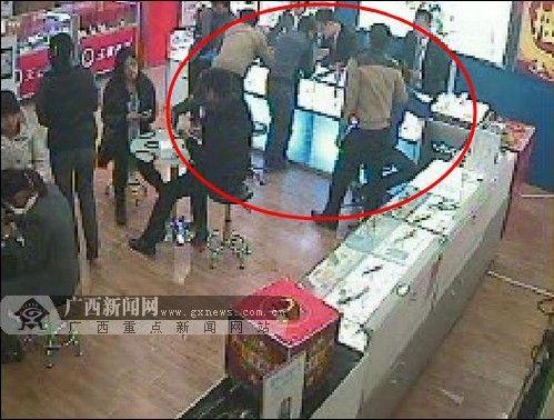 1月24日晚8时许,王者通讯店内监控视频显示,在店员拾到饰品的手机柜台前围拢着不少顾客。(视频截图)