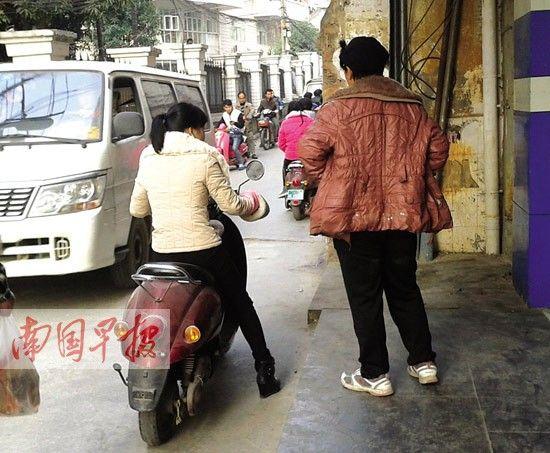 """一女子(右)正向顾客介绍购买""""黑车""""如何上牌。"""