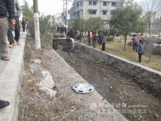 图为翻下路沟的小车。
