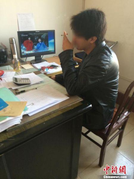 1月30日,合浦县教育局的一名工作人员在办公室内悠闲地边抽烟边用电脑看电视剧。 陈燕 摄
