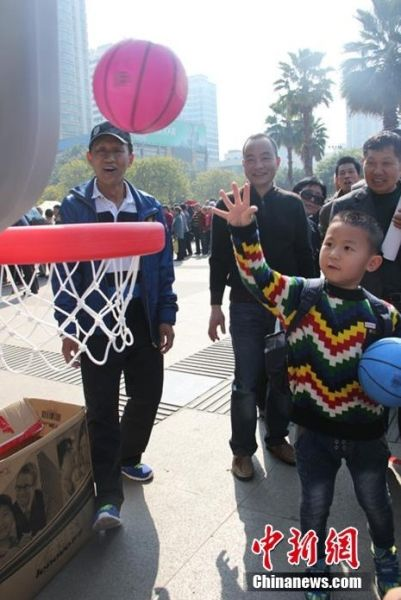 图为广西柳州春节游园会现场,一名小孩子在投篮。朱柳融 摄