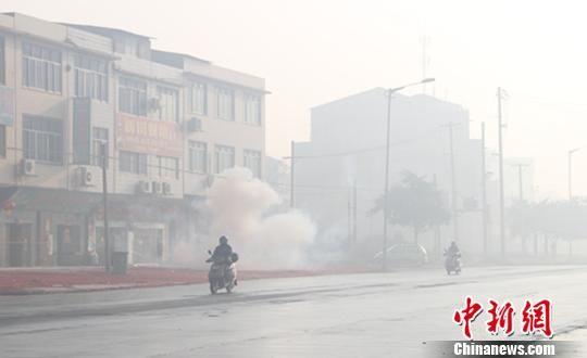 图为当地居民在浓雾中放鞭炮。朱柳融 摄