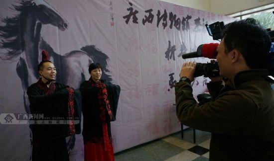 一对年轻人穿上传统汉服面对电视摄像机拜年。广西新闻网记者 邓昶摄