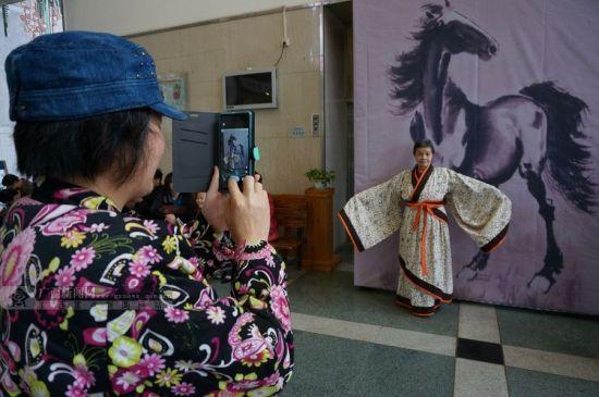 一名老人穿上汉服,她的同伴拿手机拍照。广西新闻网记者 邓昶摄