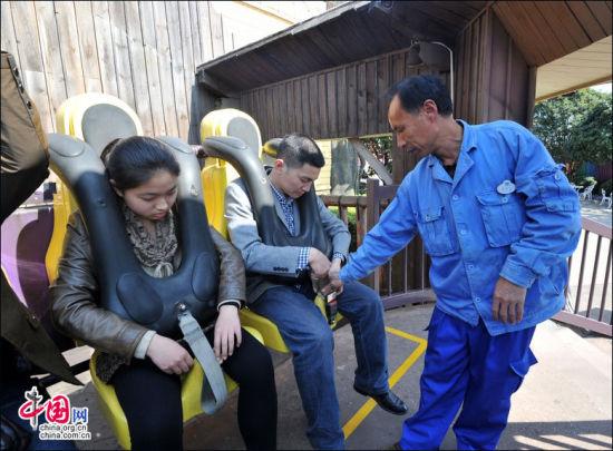 图为兴安乐满地度假世界的员工刘平元在检查游客的安全带。