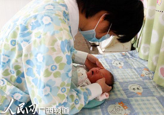 图为护士给刚出生的宝宝做抚触按摩。杨璐溦 摄