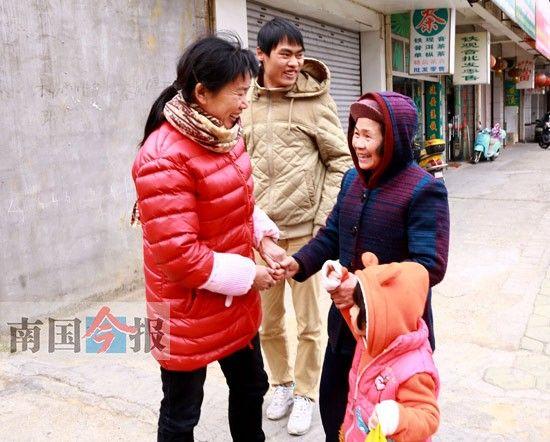 黄渊源(中)的亲生母亲唐桂英(左),拉着黄的养母江小英(右)的手,热情攀谈起来。 记者 王缉宁 摄