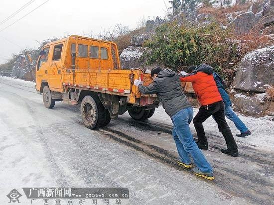2月11日,在全州县白宝乡公路上,众人帮助打滑的汽车前行。王滋创 李宗和 摄