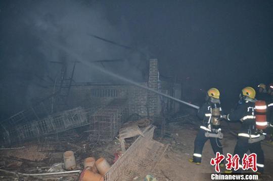 图为消防官兵铺设水带灭火。图片来源:中国新闻网
