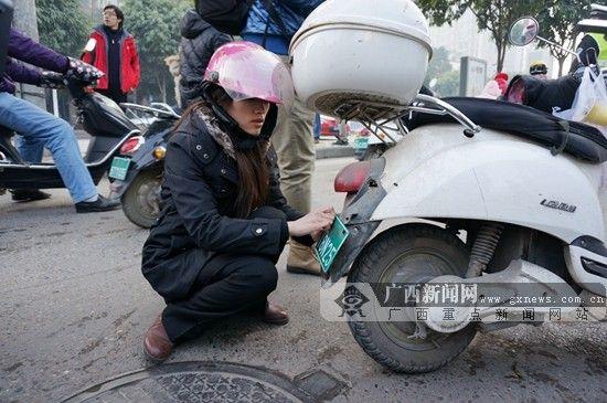 有些市民虽上了牌,却没有悬挂号牌,在接受教育后,当即自行安装号牌。广西新闻网记者 刘斐 摄