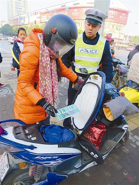 见交警查车,这名女车手马上翻出未悬挂的号牌。记者 刘治理 摄