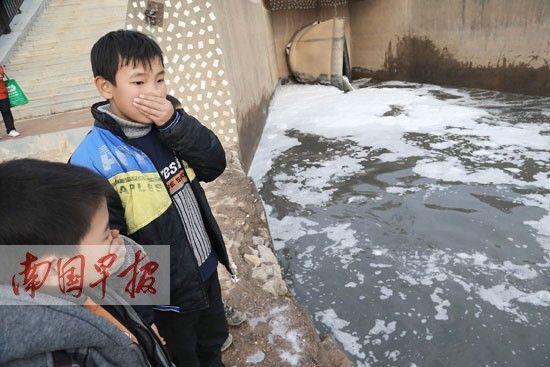 由于排出的污水太臭,两名儿童用手捂住自己的鼻子。