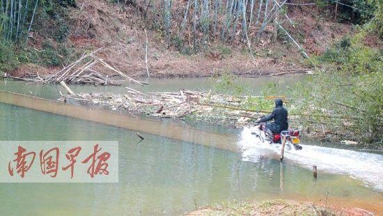 一村民驾着摩托车冒险冲过危桥。记者 谢奎 摄