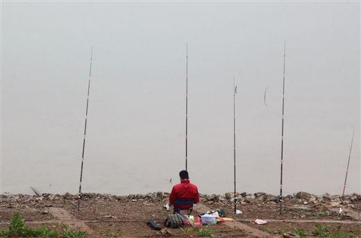 南宁邕江边,一名市民在大雾天气中钓鱼。当代生活报记者 何学俏摄