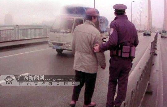 为保证老人安全,民警搀扶刘先生向人行道走去。南宁市公安局巡警支队供图