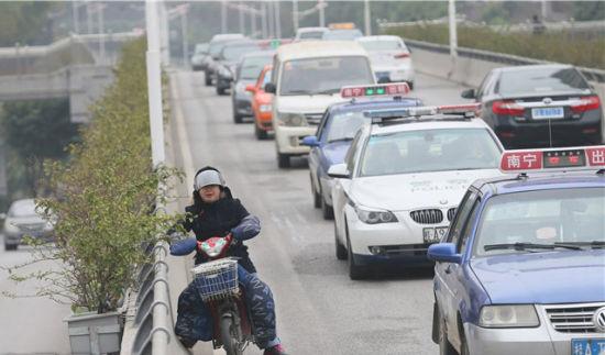 一名电动车手看到交警,不敢继续行驶,准备掉头离去。