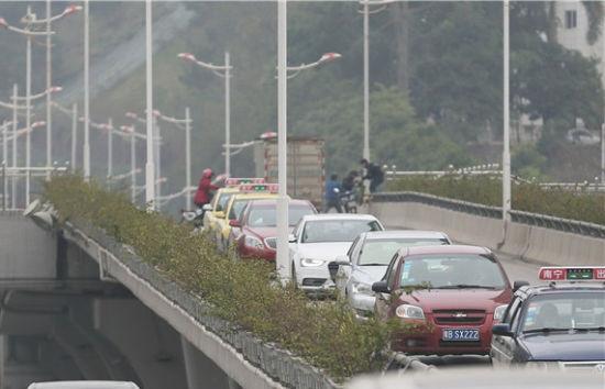 几名电动车手扛车翻越隔离栏。