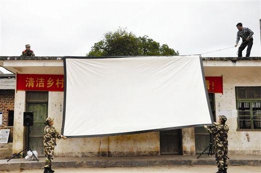 峙浪边防派出所的民警与韦柯(右上)一起固定电影幕布