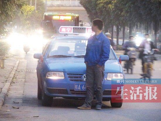 一出租车司机正在用身体挡车牌。