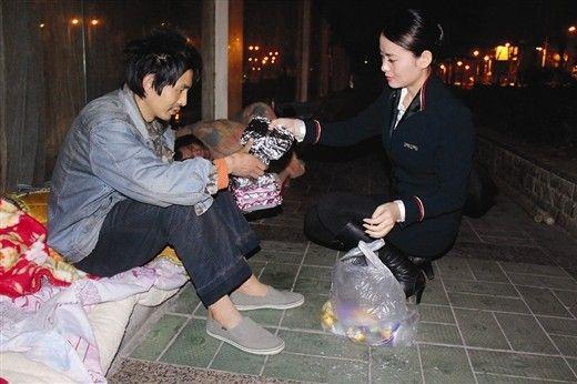 """空姐王珊珊把食物递给流浪者""""向上""""。记者 姜锋摄"""