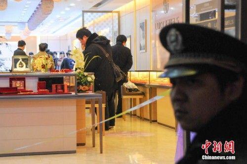 一名头戴鸭舌帽的持刀男子在朝阳路一家金店砸开柜台并抢走1000多克价值约29.8万元人民币金饰。洪坚鹏 摄