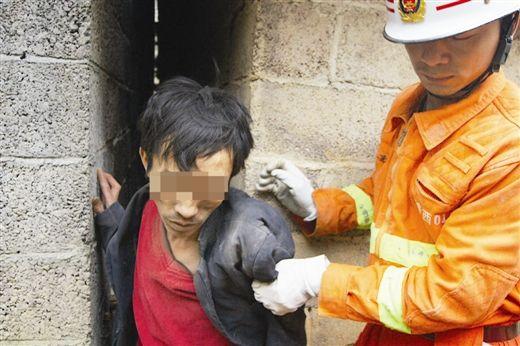 消防人员从狭窄的墙缝中救出被困男子。 谷宜超 周小龙 摄